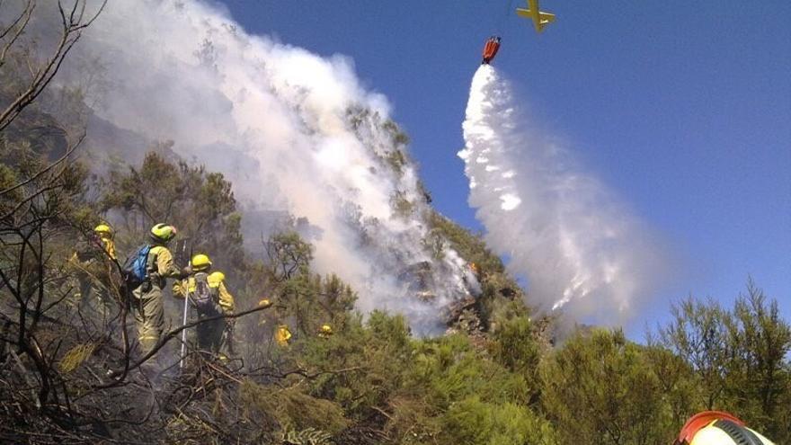 Un helicóptero hace una descarga de agua en una zona donde intervienen efectivos de la Brif. Foto cedida/Europa Press