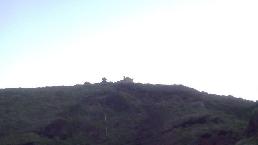En la imagen, al fondo, el desprendimiento registrado en una ladera de la carretera de Tenagua a Martín Luis, en Puntallana. Foto: BOMBEROS LA PALMA.