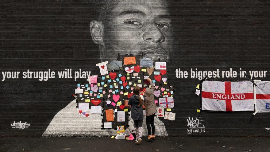 Dos personas colocan mensajes de apoyo encima de los insultos contra el jugador inglés Marcus Rashford.