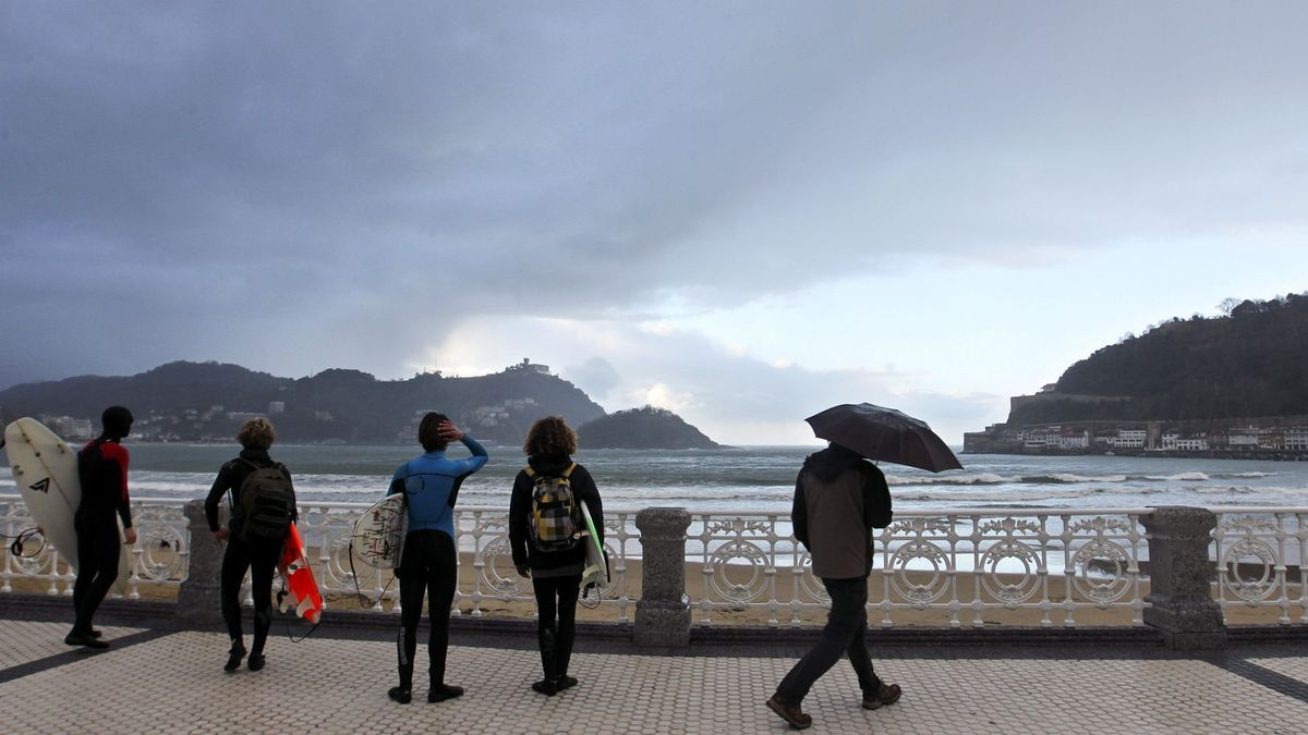 Un grupo de surfistas observa el oleaje en la playa de la Concha de San Sebastián.