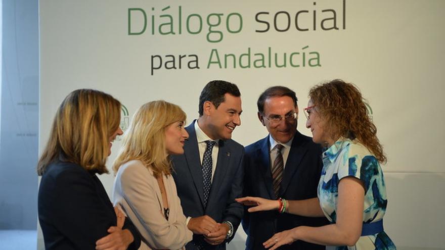 El presidente andaluz, Juan Manuel Moreno, con la líder regional de CCOO, Nuria López, la de UGT, Carmen Castilla, el presidente de la patronal, Javier González de Lara, y la consejera de Empleo, Rocío Blanco.