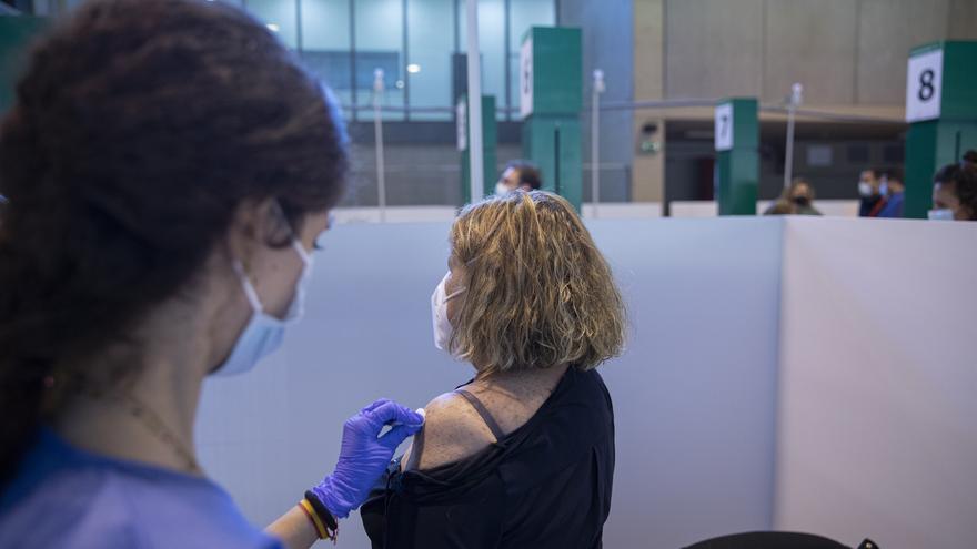 Archivo - Una sanitaria vacuna a una mujer durante la primera jornada de vacunación ante la Covid-19 en el Estadio de La Cartuja de Sevilla, foto de archivo