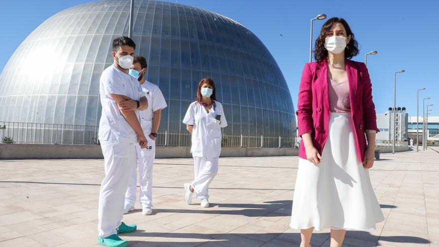 La presidenta de la Comunidad de Madrid, Isabel Díaz Ayuso, junto a varios profesionales sanitarios, durante su visita al inicio del proceso de vacunación contra el COVID-19 que se ha puesto en marcha en el Pabellón 3 del Hospital Público Enfermera Isabel