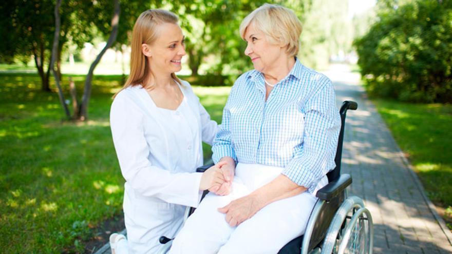 Una voluntària ajudant a una persona amb mobilitat reduïda.