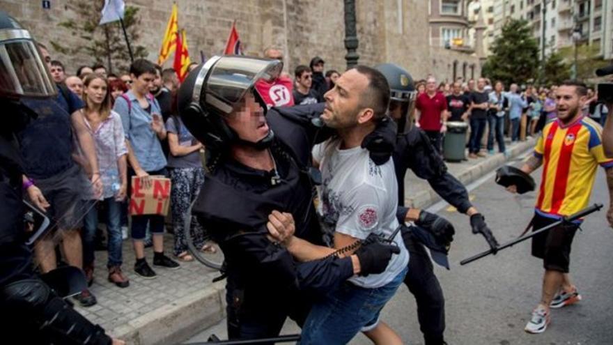 Uno de los agresores es retenido por un policía nacional antes de la manifestación.