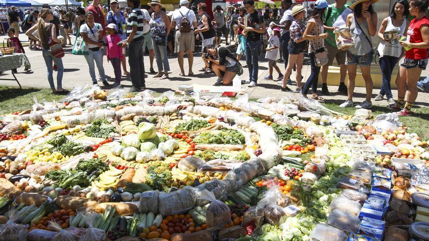 La gente observa una instalación hecha con alimentos encontrados en la basura en un parque de San Diego, EEUU.