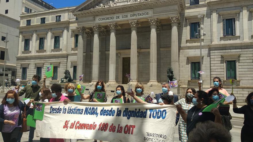 Varias trabajadoras despliegan una pancarta para exigir derechos laborales frente al Congreso y varios diputados, a los que han entregado escobillas del baño.