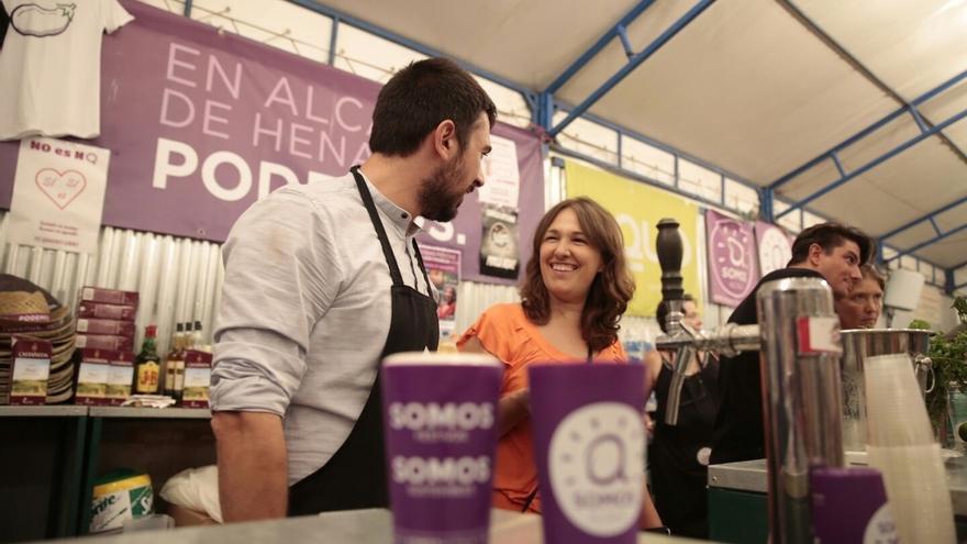 Los diputados Ramón Espinar y María Espinosa, tras la barra de la caseta de Podemos en las fiestas de Alcalá