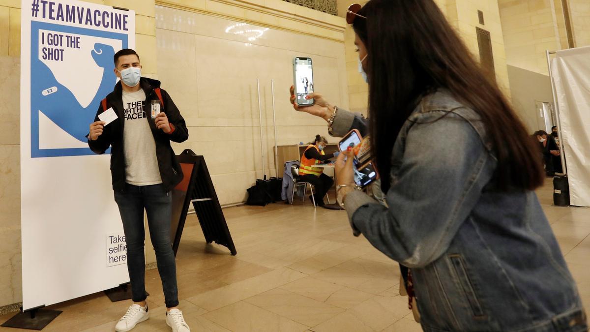 Un hombre posa para una foto después de vacunarse contra la COVID-19 en la estación Grand Central Terminal de Nueva York.