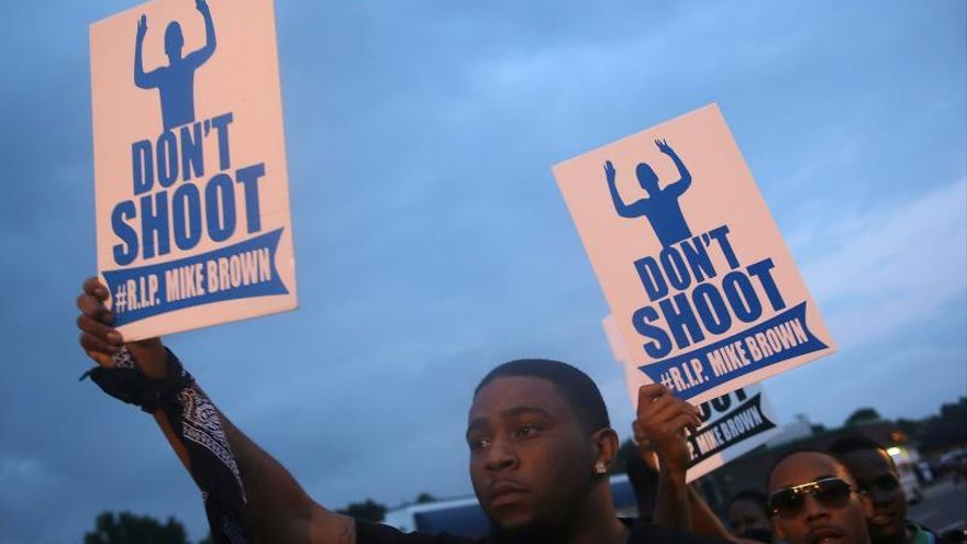Demonstrators hold signs as protests continues after the shooting death of Michael Brown in Ferguson, Missouri, USA, 17 August 2014.