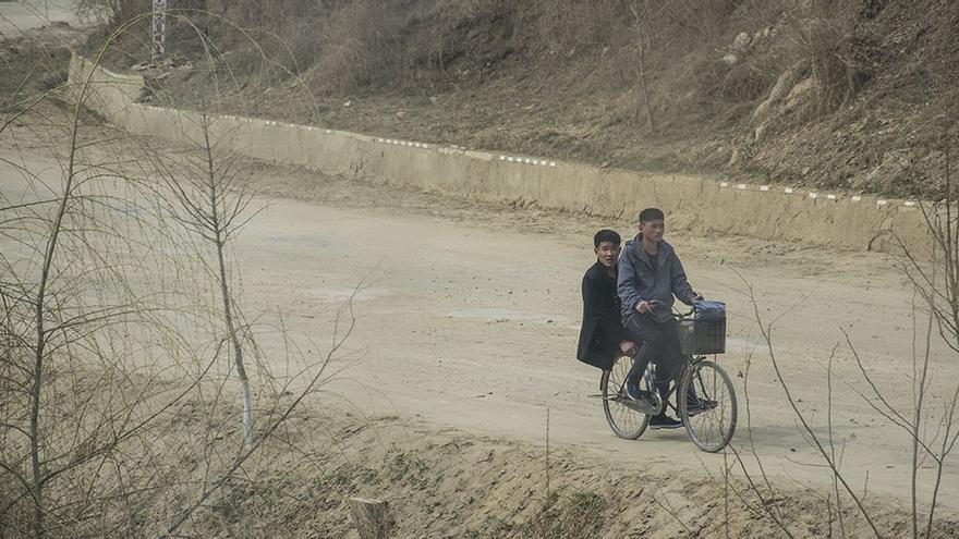 Aldeanos compartiendo una bicicleta. (CA).
