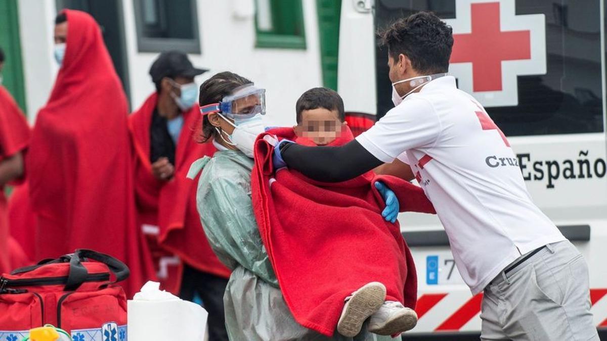 Un voluntario de la Cruz Roja abriga con una manta a un niño llegado en patera a Lanzarote