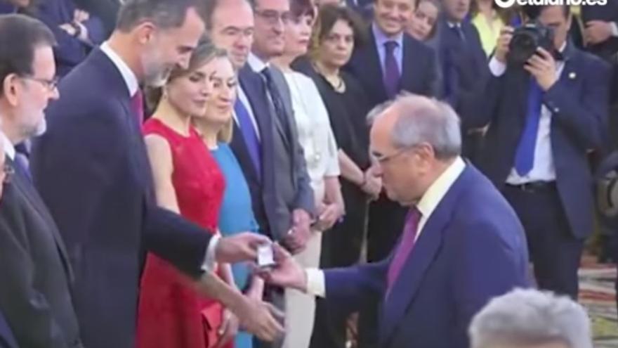 Martín Villa recibe la medalla de manos del rey.