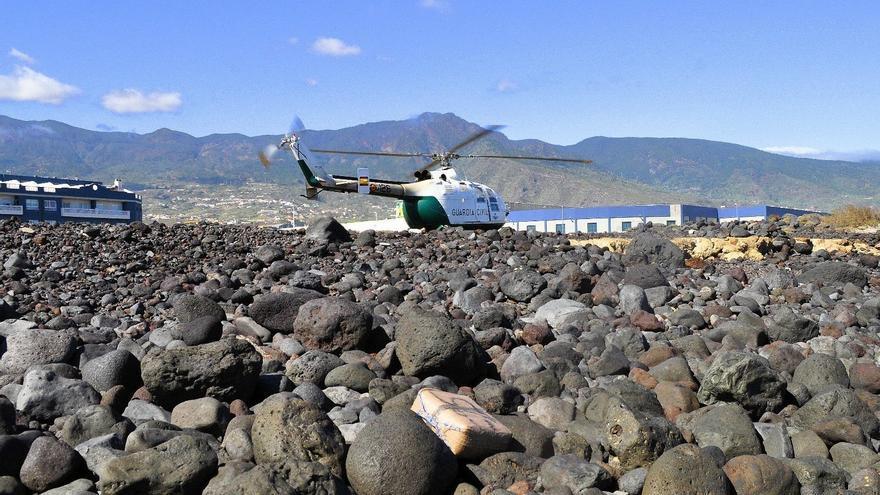 El helicóptero de la Guardia Civil junto a uno de los fardos de droga localizados en el litoral de Tenerife.