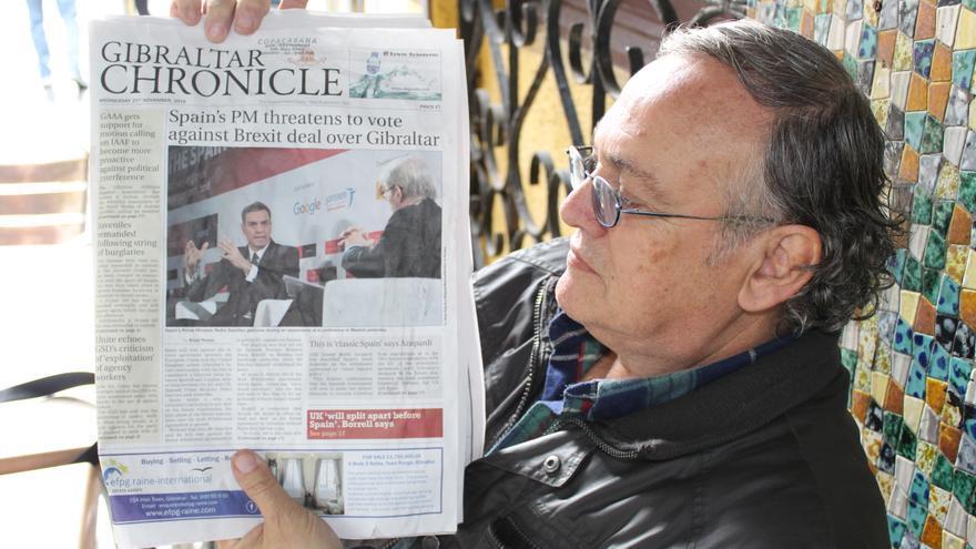 Un ciudadano gibraltareño muestra un periódico local con Pedro Sánchez en su portada.