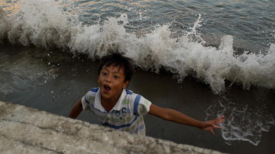 Un niño juega a refugiarse de las olas del mar en Tacloban (Filipinas). Foto: Carlos Sardiña Galache.