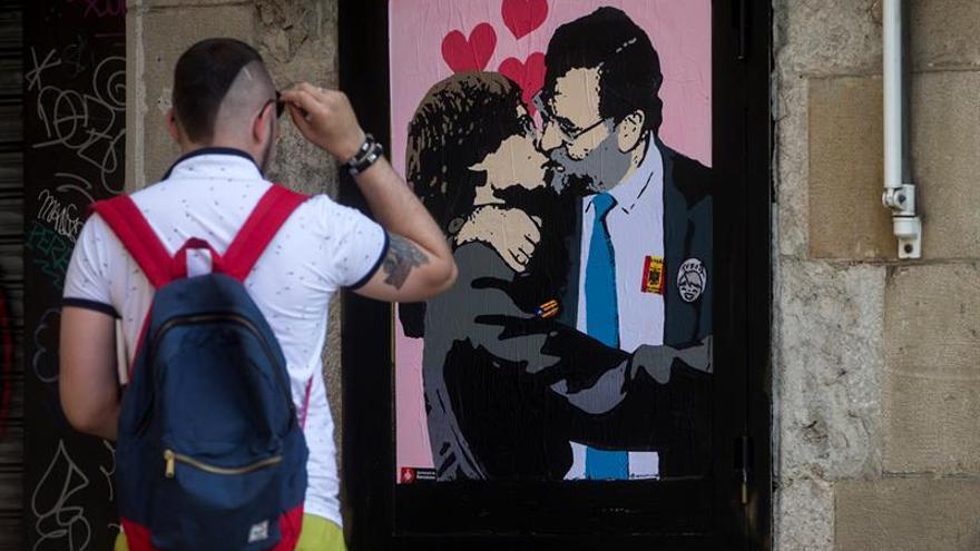 Un artista urbano pinta a Rajoy y Puigdemont besándose cerca de la Generalitat
