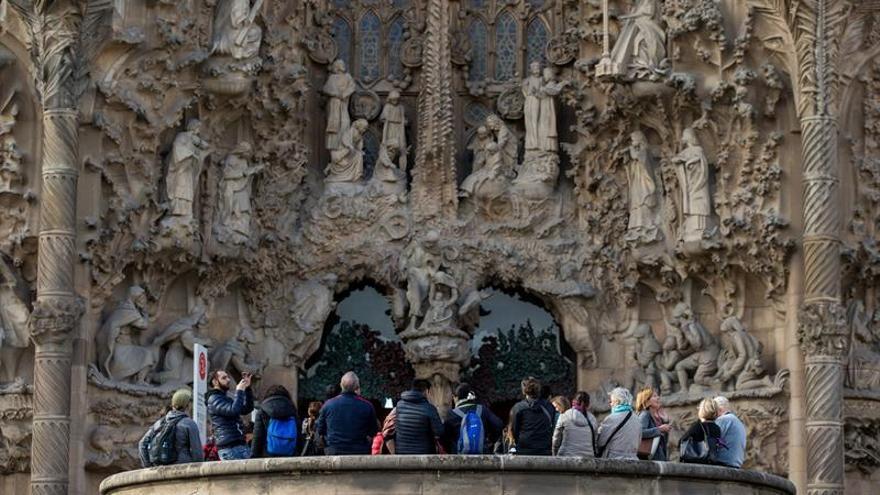 Un grupo de turistas admiran la fachada de la Sagrada Familia, en Barcelona.
