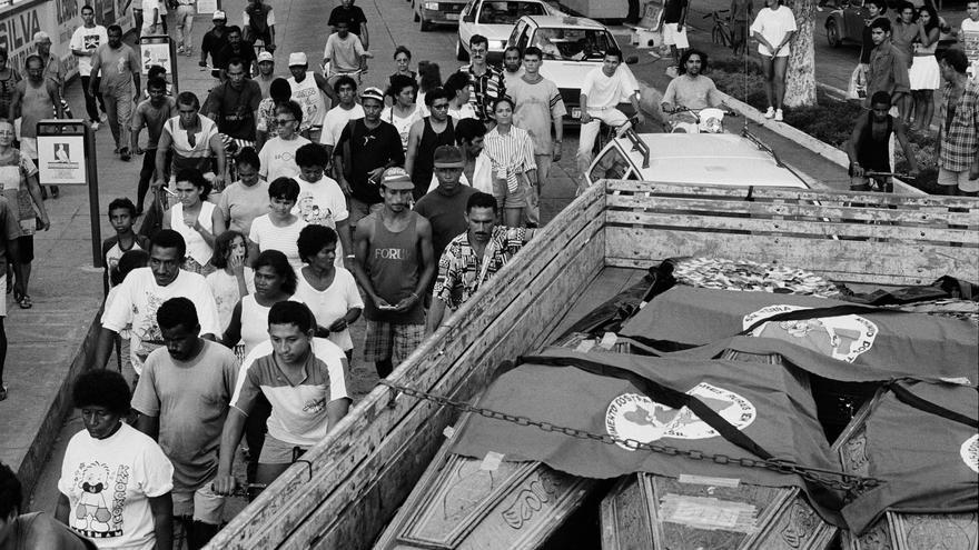 Los miembros del Movimiento de los Trabajadores Rurales sin Tierra (MST) marchaban a la ciudad de Belem, cuando cerca de 150 agentes, sin uniformes ni placas identificativas, se acercó para detener la marcha. Armados con rifles cargados con munición real, la acción represiva se saldó con la muerte de 19 personas. En la imagen, un camión se lleva los cuerpos de las víctimas desde Marabá, camino a Curionópolis. La gente continúa su vida en la calle © João Roberto Ripper