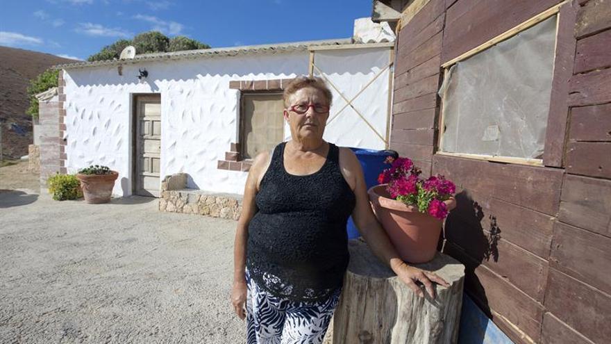 Josefa Fernández junto a la vivienda en la que vive con su familia, construida en un espacio protegido en el Parque Rural de Betancuria, en Fuerteventura (EFE/CARLOS DE SAÁ)
