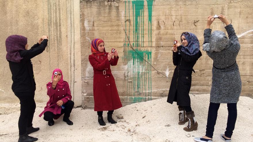 Algunas de las jóvenes sirias del campamento de Za'atari que participaron en el taller de vídeo de la cineasta Laura Doggett posan con sus cámaras. | Foto cedida a eldiario.es.