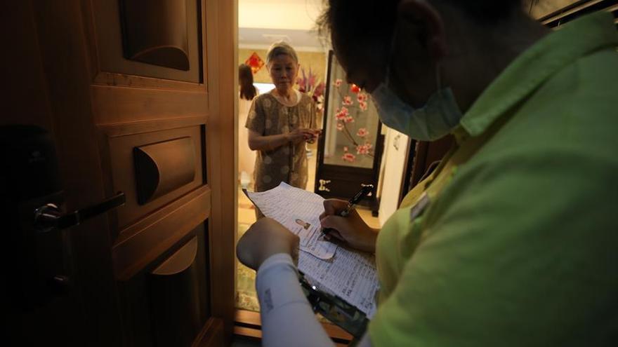 Un trabajador comunitario toma notas durante una visita a domicilio con trabajadores médicos para hacer pruebas a los residentes para detectar el nuevo coronavirus en Wuhan en la provincia de Hubei en el centro de China, el 14 de mayo de 2020. La ciudad planea hacer la prueba a todos sus ciudadanos, más de 10 millones de personas, en un plazo de 10 días.