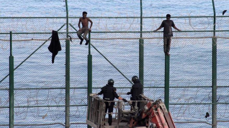 Uno de los participantes en el salto es detenido este viernes por la Policía española en la valla fronteriza de Ceuta con Marruecos.