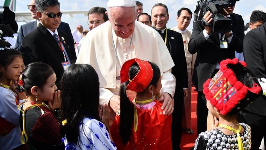 El papa Francisco saluda a un grupo de niños vestidos con trajes tradicionales a su llegada al aeropuerto internacional de Rangún (Birmania), este 27 de noviembre.