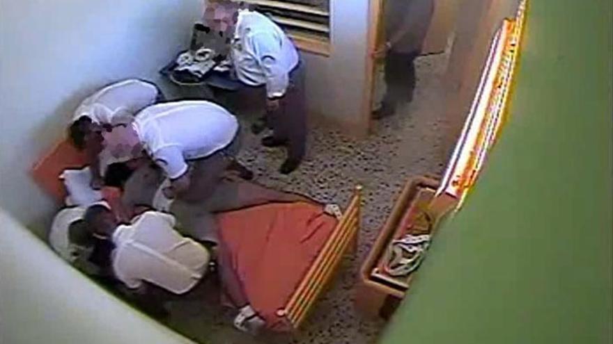 Miembros de seguridad atando al joven a la cama