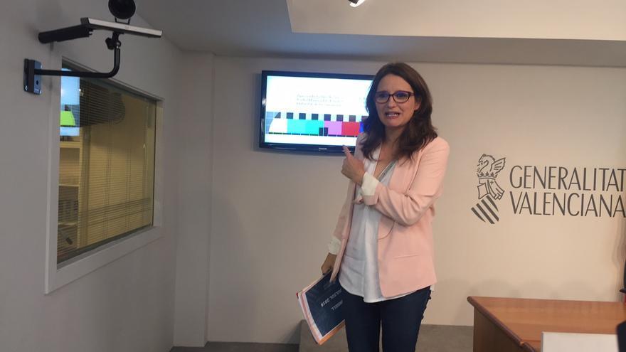 La vicepresidenta del Consell, Mónica Oltra, junto a la nueva imagen que aparece en el dial que ocupaba Canal 9.