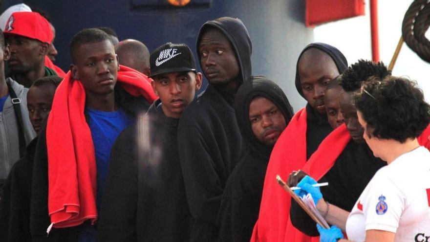 Personal de Cruz Roja atiende a un grupo de inmigrantes en Almería