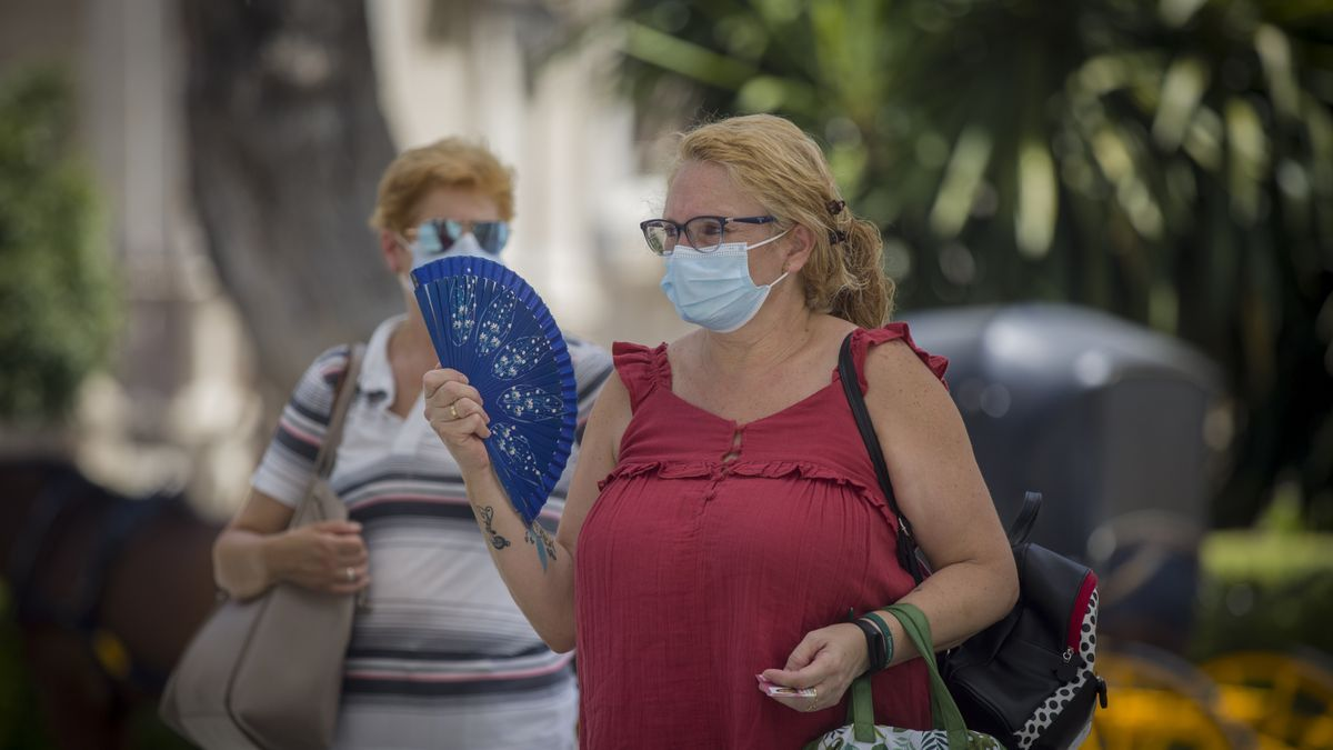 Una mujer con mascarilla se abanica en la calle