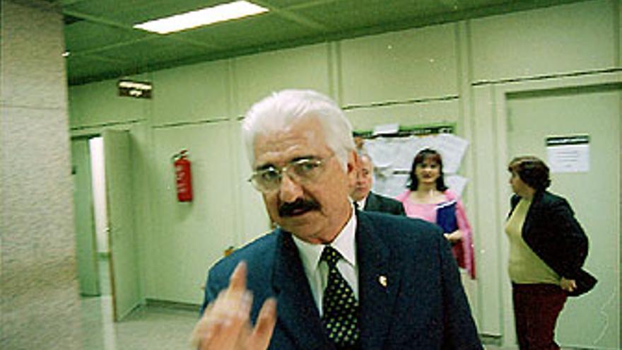 Suárez Gil, en una imagen de archivo en los juzgados de Granadera Canaria. Abajo: reunión empresarial en su casa, con trofeos de caza colgados de las paredes del salón.