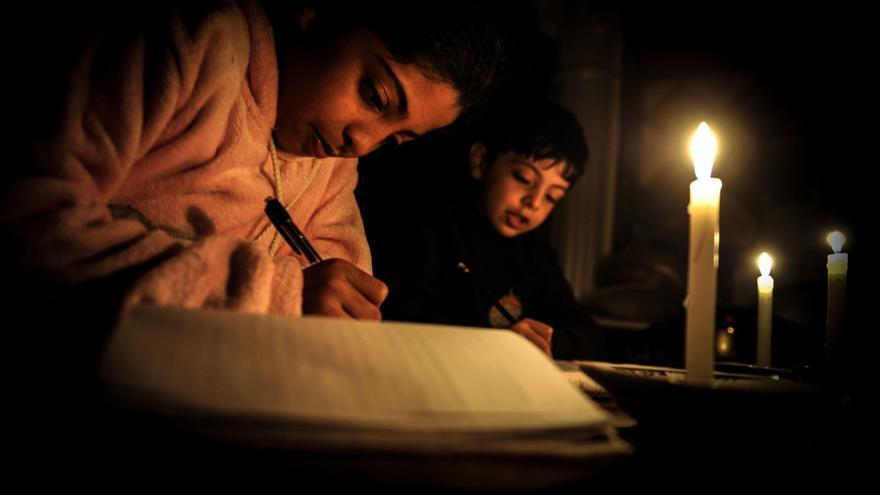 Los cortes de electricidad obligan a los niños y niñas refugiadas de Palestina a tener que a hacer sus deberes a la luz de las velas.