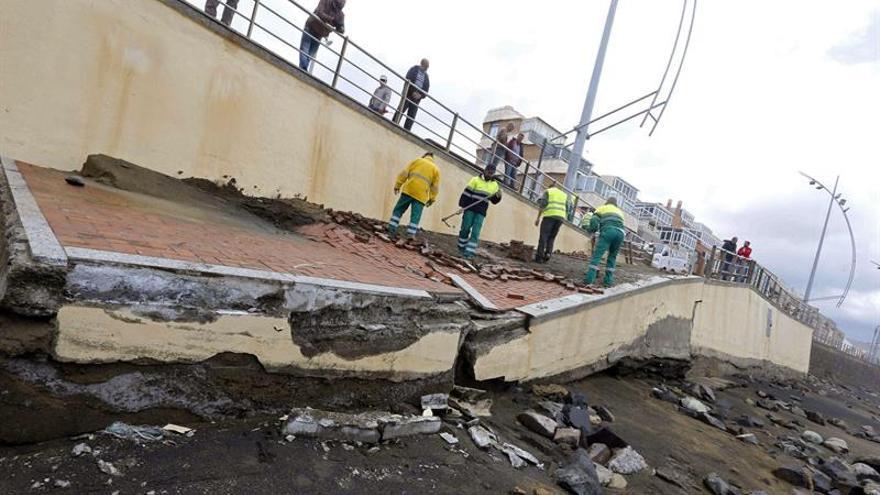 Operarios del Ayuntamiento de Las Palmas de Gran Canaria reparan los desperfectos causados por el fuerte oleaje en varios de los accesos de la playa de Las Canteras, donde se han producido un desnivel de metro y medio. EFE/Elvira Urquijo A.