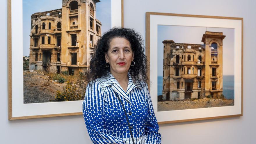 La artista Zineb Sedira delante de la serie de fotografías Haunted Houses, 2006.