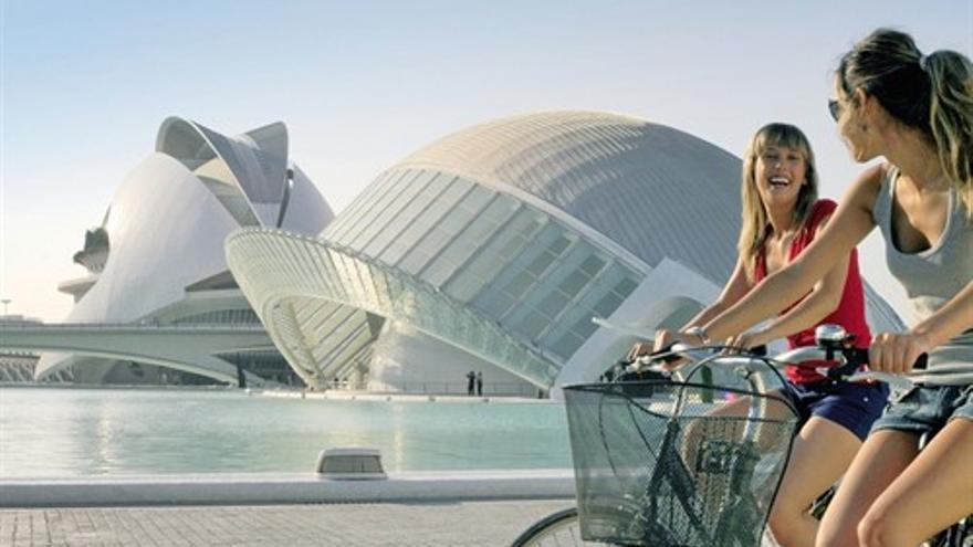 Dos jóvenes en bicicleta con la Ciudad de las Artes y las Ciencias de Valencia