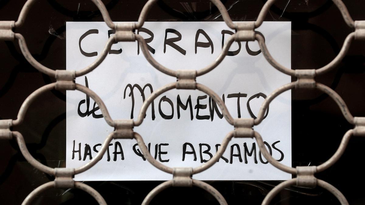 """Detalle de un cartel colgado en la fachada de una tienda con el lema """"Cerrado de momento hasta que abramos""""."""