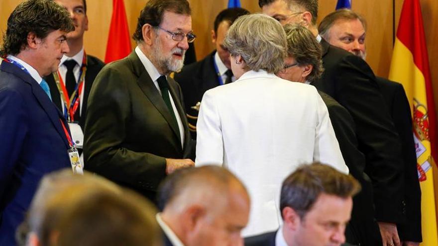 Rajoy conversa con la primera ministra británica, Theresa May.