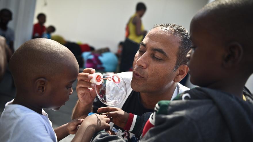 El mediador cultural de MSF Ahmad Al Rousan juega con un niño que acaba de ser rescatado en la cubierta del Bourbon Argos // Copyright: Sara Creta/MSF
