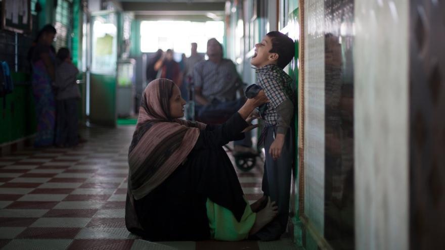 Una madre ayuda a su hijo a vestirse en el pasillo de la escuela. 700 niños son atendidos por los profesionales de la escuela / foto: Bernat Parera