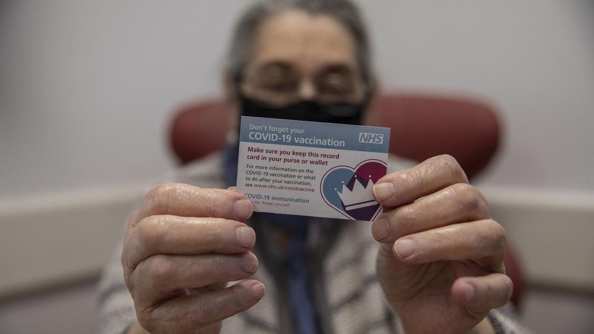 Bernice Wainer, de 82 años, muestra su tarjeta de vacunación tras recibir la dosis en un hospital de Londres.