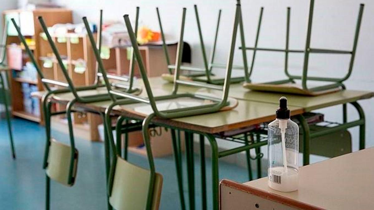 Un aula vacía con gel desinfectante.