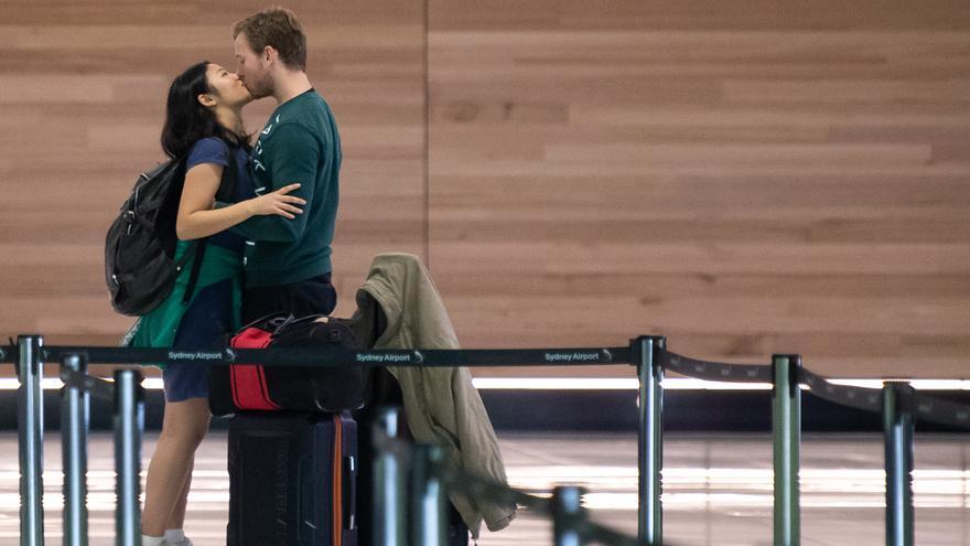 Una pareja se abraza en la zona de salidas del Aeropuerto Internacional de Sydney, Australia.