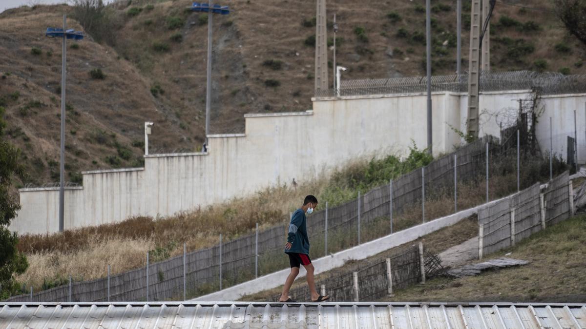 Un niño camina por un tejado junto a la frontera de Ceuta.