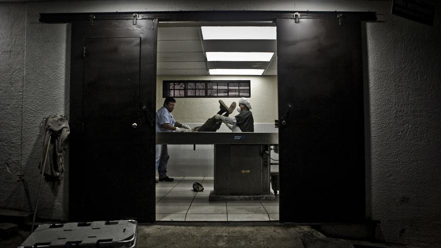 Dos empleados de Medicina Legal mueven un cadáver en la sala de autopsias para iniciar la inspección postmortem. /Edu Ponces (RUIDO Photo)