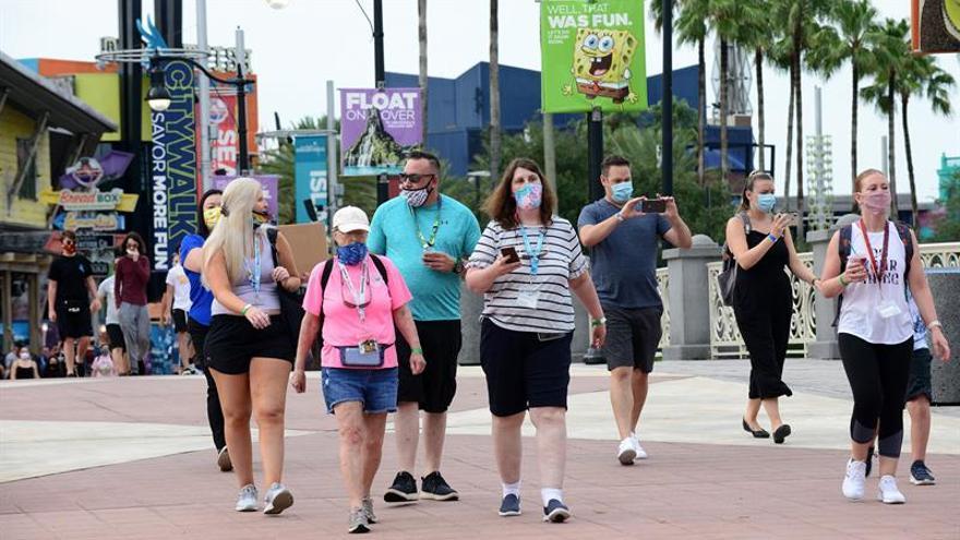 Varias personas con tapabocas caminan por el parque temático de Universal Studios en Orlando, Florida (EE.UU).