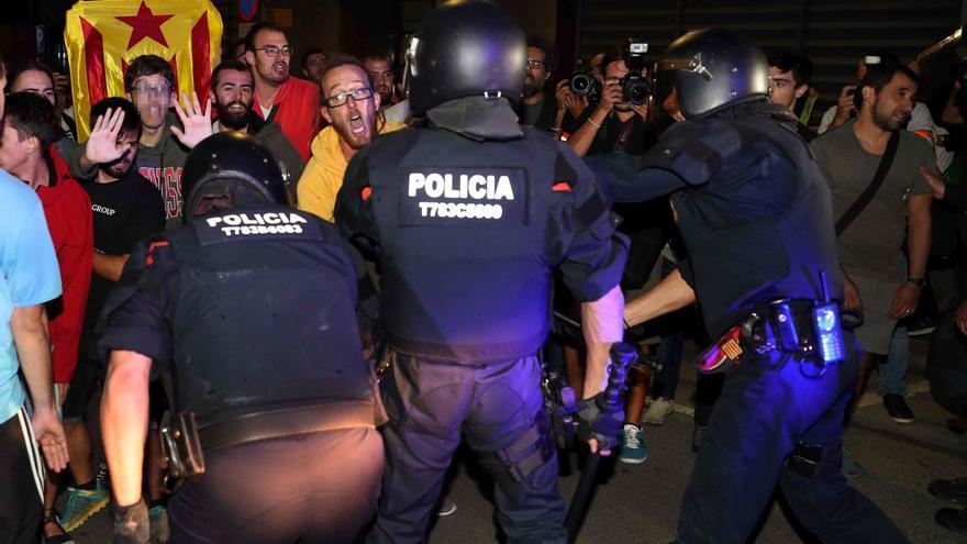 Los Mossos contienen a los manifestantes a la salida de la comitiva de la Guardia Civil tras el registro a Unipost en Terrassa en septiembre de 2017.