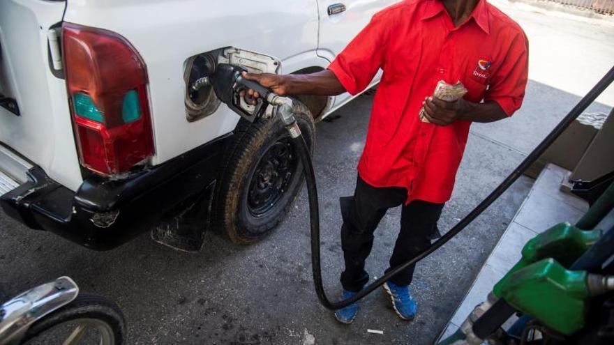 Un trabajador pone gasolina en un vehículo este jueves en una gasolinera de Puerto Príncipe (Haití). El agua potable escasea desde que se desataron las virulentas protestas contra del presidente, Jovenel Moise, el pasado 16 de septiembre, ya que los repartidores, si consiguen diésel para sus camiones, no logran cruzar las barricadas que, casi a diario, congestionan las principales vías de las grandes ciudades.