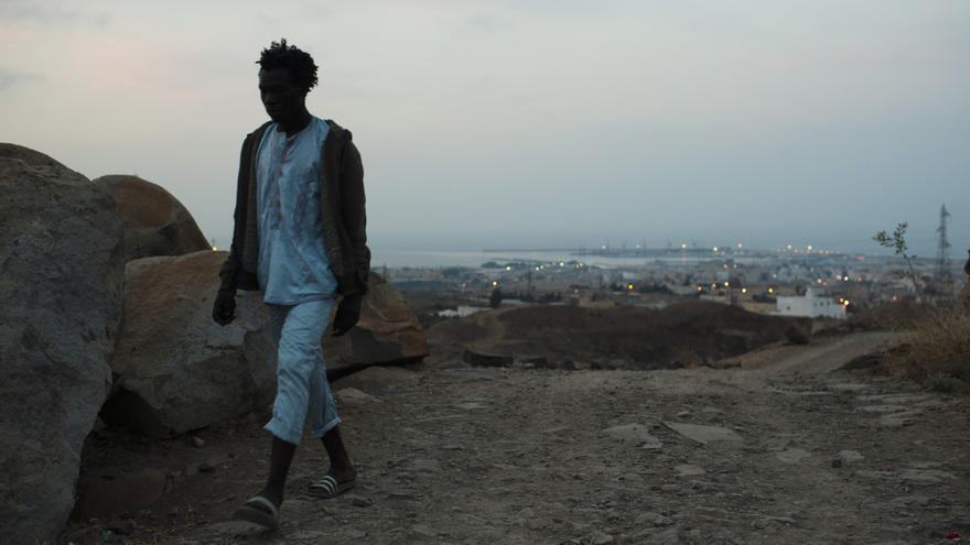 Adil Hamid, 25, de Camerún, camina por el monte Gurugú con Melilla a su espalda. /Fotografía: Ángel Navarrete.